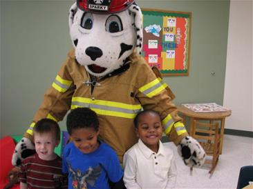 Three children being hugged by Sparky the Firedog