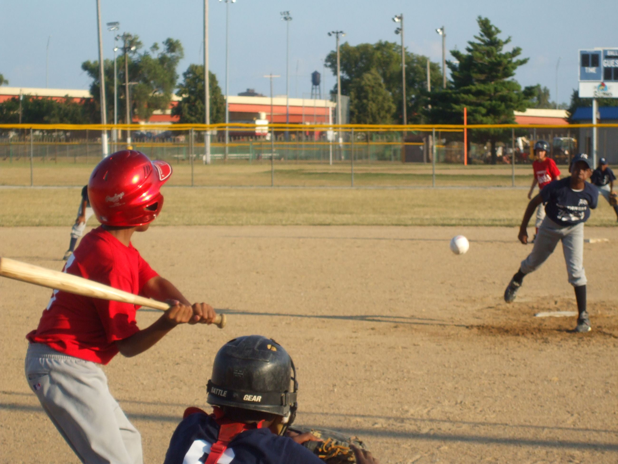 Baseball being pitched with child ready to swing bat