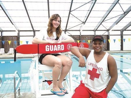 Two lifeguards at lifeguard stand with pool in background