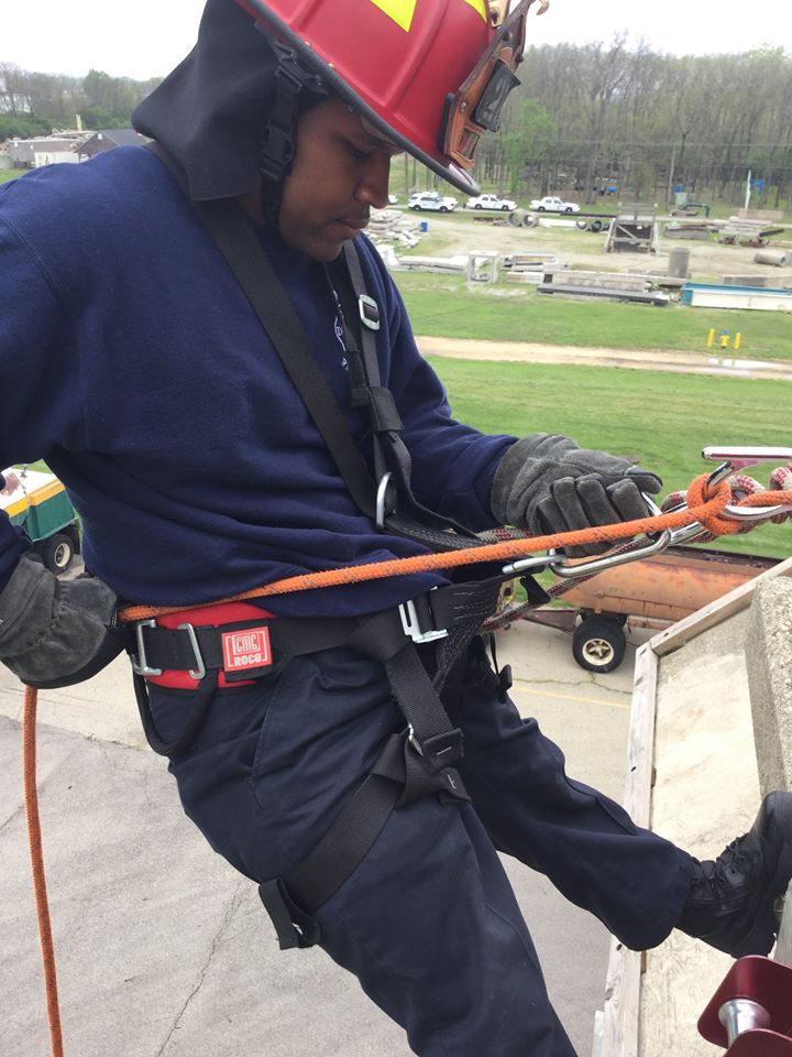 Fire recruit rappelling building